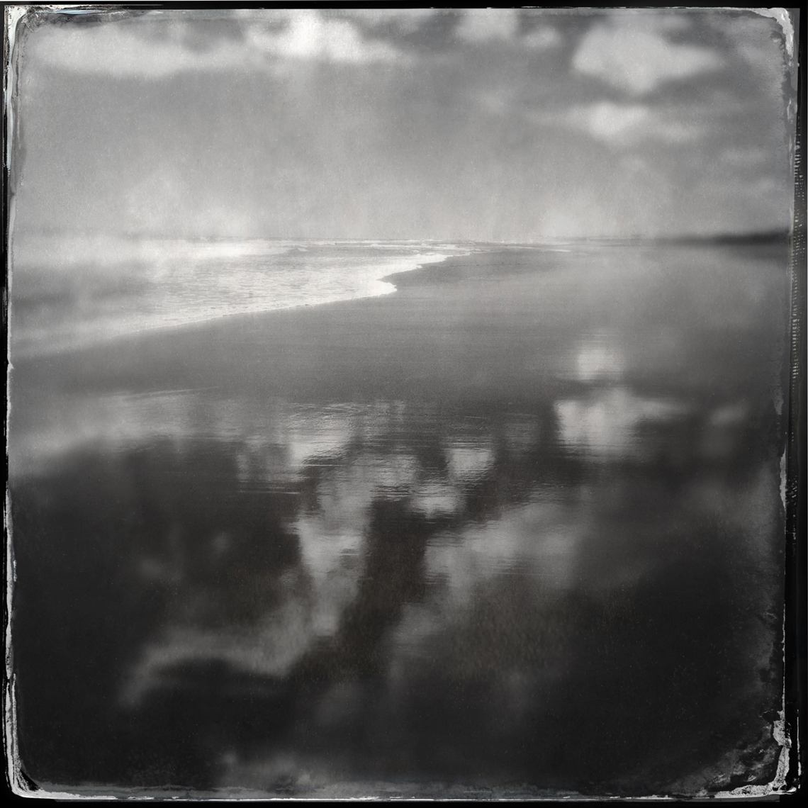 Jon Wyatt Photography - Wet sand on beach reflecting clouds. Hipstamatic