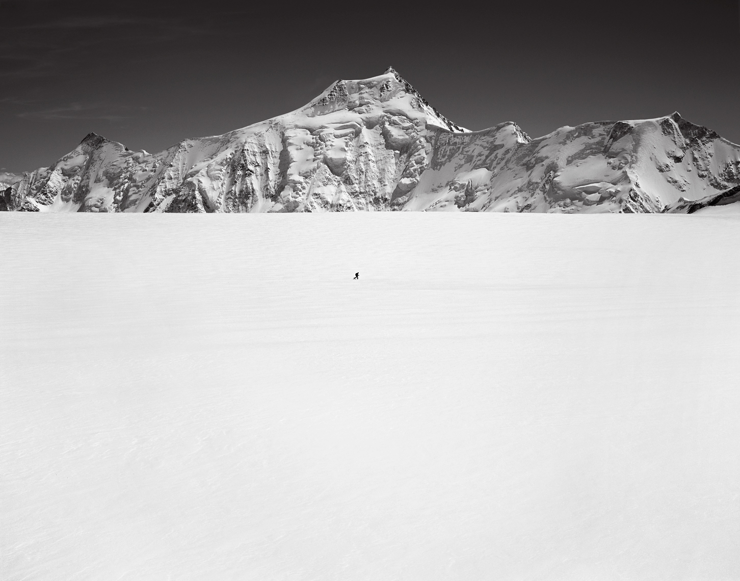 Jon Wyatt Photography - Solo ski tourer in front of Finsteraarhorn mountain, Bernese Oberland,  Switzerland