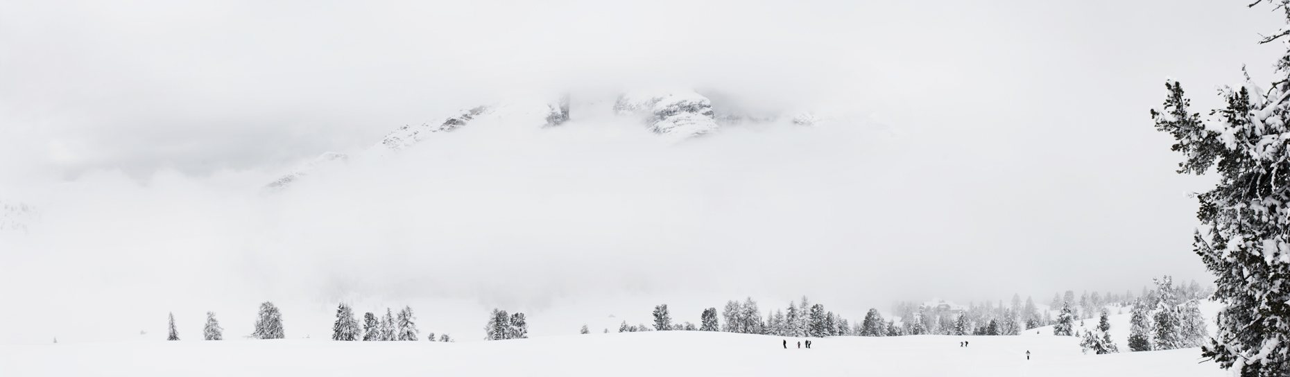 Jon Wyatt Photography - Walkers in snow with cloudy mountains, Italy